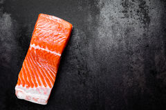 Raw salmon or trout sea fish fillet on black metal background, top view Royalty Free Stock Images