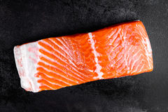 Raw salmon or trout sea fish fillet on black metal background, top view Stock Photography
