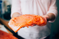 Raw salmon in woman hands Stock Images