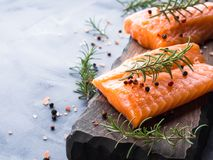 Raw salmon on wooden board with herbs Stock Photo