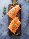 Raw salmon on wooden board with herbs Royalty Free Stock Photo