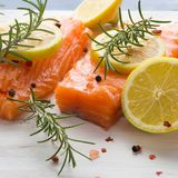 Raw salmon on wooden board with herbs Royalty Free Stock Image