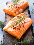 Raw salmon on wooden board with herbs Stock Photography