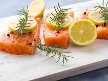Raw salmon on wooden board with herbs Royalty Free Stock Photos