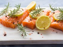 Raw salmon on wooden board with herbs Stock Images