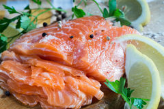 Raw salmon on wooden board. Raw salmon with spices on wooden board Stock Photos