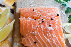 Raw salmon on wooden board. Raw salmon with spices on wooden board Stock Photo
