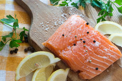 Raw salmon on wooden board. Raw salmon with spices on wooden board Stock Photography