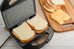 Raw sandwiches in panini press. And ingredients on wooden cutting board. Simple recipe of a lunch meal stock photo