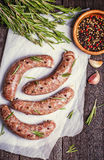 Raw sausage of beef and pork with spices. On the white wrapping paper Stock Image