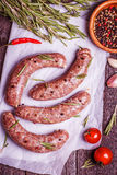 Raw sausage of beef and pork with spices. On the white wrapping paper Royalty Free Stock Photos