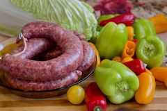 Raw sausage and colorful vegetables. Products for a typical Balkan dish - stuffed peppers and  cabbage leaves  With minced meat, rice, leeks and spices Stock Image