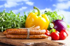 Raw sausage, fresh herbs and vegetables. On wooden table and nature background Stock Images