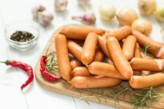 Raw sausage for frying on a cutting board with rosemary and spices on a white wooden rustic background stock photos