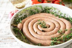 Raw sausage for frying Grilled on vintage pan With thyme and tom Stock Photography