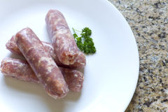 Raw Sausage. Raw Italian sausage on a white plate with parsley ready to cook Stock Images
