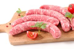 Raw sausage. And tomato on board Royalty Free Stock Image