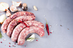 Raw sausage with spices. On a gray stone background Stock Photo