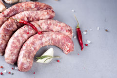 Raw sausage with spices. On a gray stone background Royalty Free Stock Photography