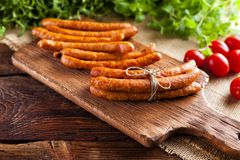 Raw sausage, tomato and fresh herbs. On wooden and canvas background Stock Image
