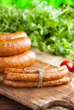 Raw sausage, tomato and fresh herbs. On wooden and canvas background Royalty Free Stock Photo