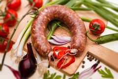 Raw sausage with vegetables on wooden board Stock Photos