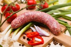 Raw sausage with vegetables on wooden board Royalty Free Stock Photos