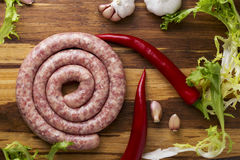 Raw sausage and vegetables. On a wooden table Stock Image