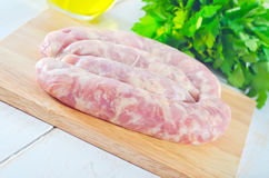 Raw sausages. On wooden board Stock Photo