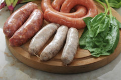 Raw sausages for a barbecue with spinach leaves on wooden plate.  Royalty Free Stock Photography