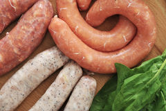 Raw sausages for a barbecue with spinach leaves on wooden plate. Top view Stock Photos