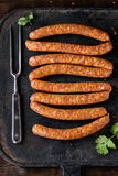 Raw sausages for BBQ. Fresh raw beef sausages with spices for BBQ on black iron board over dark wooden background with salt, herbs, pepper and big meat fork. Top Royalty Free Stock Photos