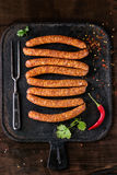 Raw sausages for BBQ. Fresh raw beef sausages with spices for BBQ on black iron board over dark wooden background with salt, herbs, pepper and big meat fork. Top Stock Image
