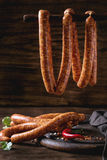 Raw sausages for BBQ. Fresh raw beef sausages with spices for BBQ hanging on stick over dark wooden background with salt, herbs and pepper Stock Photos
