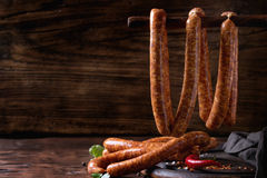 Raw sausages for BBQ. Fresh raw beef sausages with spices for BBQ hanging on stick over dark wooden background with salt, herbs and pepper. With space for text royalty free stock images