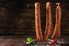 Raw sausages for BBQ. Fresh raw beef sausages with spices for BBQ hanging on stick over dark wooden background with salt, herbs and pepper. With space for text Stock Photos