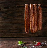 Raw sausages for BBQ. Fresh raw beef sausages with spices for BBQ hanging on stick over dark wooden background with salt, herbs and pepper. Square image stock photos