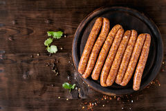 Raw sausages for BBQ. Fresh raw beef sausages with spices for BBQ on wood chopping board over dark wooden background with salt, herbs and pepper. Top view. Copy royalty free stock image