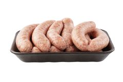 Raw sausages on black foam tray. Isolated. On white. Side view royalty free stock photo