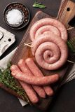 Raw sausages. Cooking on wooden cutting board. Top view Royalty Free Stock Photos
