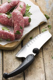 Raw Sausages on Cutting Board and Butcher Knife Stock Photo