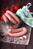 Raw sausages in dipper. Raw sausages, tomatoes and spices stock images