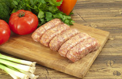 Raw sausages and fresh vegetables on a table Stock Photo