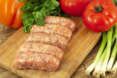 Raw sausages and fresh vegetables on a table Royalty Free Stock Images