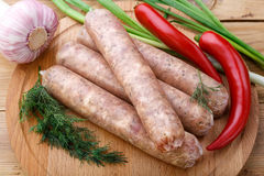 Raw sausages for frying on a wooden board with vegetables and dill. Several raw sausages from pork with beef for grilling lie on a wooden board, close-up. Red stock photography
