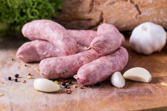 Raw Sausages. With garlig and spices on the cutting board Royalty Free Stock Photos