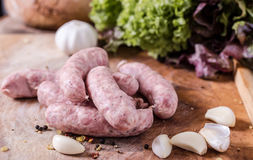 Raw Sausages. With garlig and spices on the cutting board Stock Photography