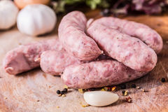 Raw Sausages. With garlig and spices on the cutting board Royalty Free Stock Image