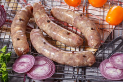 Raw sausages on the grill grate. Royalty Free Stock Image