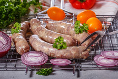 Raw sausages on the grill grate. Royalty Free Stock Photos